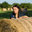 A woman and a stack of straw — Stock Photo