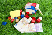 Small house of children's blocks, the money lying in the grass. — Stock Photo