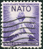 Postage stamp printed in the USA, dedicated to the 3rd anniversary of the signing of the North Atlantic Treaty Organization, shows Torch of Liberty and Globe — Stock Photo