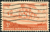 Postage stamp printed in the USA, dedicated to the centennial of the Establishment of the Kansas Territory, shows Wheat Field and Pioneer Wagon Train — Stock Photo