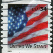 "Postage stamp printed in the USA, shows a national flag of the United States, the text ""United We Stand"" — Stock Photo"