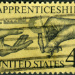 Stock Photo: Postage stamp printed in USA, dedicated to Natl. Apprenticeship Program and 25th anniv. of Natl. Apprenticeship Act, shows Machinist Handing Micrometer to Apprentice