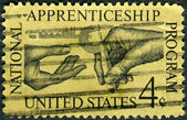 Postage stamp printed in USA, dedicated to the Natl. Apprenticeship Program and 25th anniv. of the Natl. Apprenticeship Act, shows Machinist Handing Micrometer to Apprentice — Stock Photo