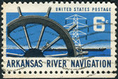 Postage stamp printed in USA, dedicated to the Opening of the Arkansas River to commercial navigation, shows Ship's Wheel, Power Transmission Tower & Barge — Stock Photo