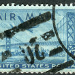 A postage stamp printed in USA, shows Plane over San Francisco-Oakland Bay Bridge — Stock Photo #38054431