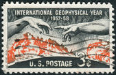 "A postage stamp printed in the USA, dedicated Geophysical Year (IGY, 1957-58), shows Solar Disc and Hands from Michelangelo's ""Creation of Adam"" — Stock Photo"
