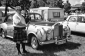 PAAREN IM GLIEN, GERMANY - MAY 19: Piper plays the Great Highland Bagpipe near the car Rolls-Royce Silver Cloud, black and white, The oldtimer show in MAFZ, May 19, 2013 in Paaren im Glien, Germany — Stock Photo