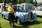 PAAREN IM GLIEN, GERMANY - MAY 19: Piper plays the Great Highland Bagpipe near the car Rolls-Royce Silver Cloud, The oldtimer show in MAFZ, May 19, 2013 in Paaren im Glien, Germany — Stock Photo