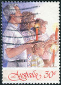 AUSTRALIA - CIRCA 1987: Postage stamp printed in Australia, Christmas Issue, shows Carols by Candlelight, Christmas Eve, Sidney Myer Bowl, Melbourne. Man, two women, boy, circa 1987 — Stok fotoğraf