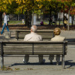 Elderly couple sitting on a bench. — Stock Photo