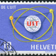 Stock Photo: SWITZERLAND - CIRC1965: Postage stamp printed in Switzerland, dedicated to Centenary of ITU, shows ITU Emblem and Atom Diagram, circ1965
