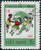Postage stamp printed in Vietnam, dedicated to International Children's Day (1977), shows Children dance around Globe — Stok fotoğraf
