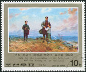 Postage stamp printed in North Korea, dedicated Revolutionary Activities of Kim Il Sung, shown With boy and man at seashore — Foto Stock