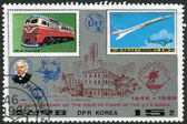 Postage stamp printed in North Korea, dedicated to 40th Anniversary of the issue of stamp of the DPR Korea, shows a diesel locomotive Kumsong and airplane Aerospatiale-BAC Concorde — Стоковое фото