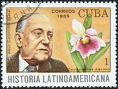 Postage stamp printed in Cuba, shows Cuban writer Alejo Carpentier and orchid Cochleanthes discolor — Stock Photo