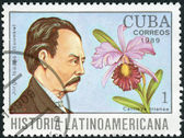 Postage stamp printed in Cuba, shows the Colombian writer Jorge Isaacs Ferrer and orchid Cattleya trianae — Stock Photo