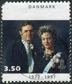 Postage stamp printed in Denmark, dedicated to the 25th anniversary of coronation Queen Margrethe II, shows Queen Margrethe II with Prince Henrik — Stock fotografie