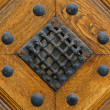 Fragment of old wooden door with grille and rivets — Stock Photo #45199459