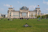 He Reichstag building and vacationers residents and visitors on the field. The Reichstag building is a historical edifice in Berlin. — Stock Photo