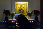 A believer lights a candle near the icons of St. Mary. The Roman Catholic Church of St. Peter and St. Paul. Built in 1870, renovated in 1950. — Stock Photo