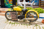 Old bike and the price of drinks in the restaurant on the waterfront. Anatolian coast - a popular holiday destination in summer of European citizens. — Stock Photo
