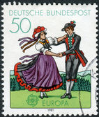 Postage stamp printed in Germany, shows South German couple dancing in regional costumes (region Black Forest) — Foto de Stock