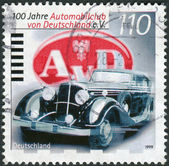 Postage stamp printed in Germany, dedicated to the centenary of the German automobile club, shows Maybach DSH Pullman and emblem of the club — Stockfoto