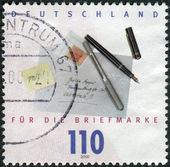 Postage stamp printed in Germany, dedicated to the Stamp Day, shows the envelope, pen and stamp — Stockfoto