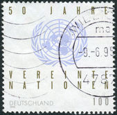 Postage stamp printed in Germany, dedicated to the 50th anniversary of the UN, shows emblem — Stockfoto