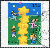 Postage stamp printed in Germany, shows children are building a tower of stars — Stock Photo