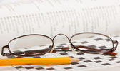 Potlood en bril op een kruiswoordpuzzel — Stockfoto
