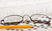 Tužka a brýle na křížovku — Stock fotografie