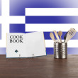 Cookbook and kitchen utensils with Greek flag — Stock Photo #34605641