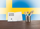 Cookbook and kitchen utensils with Swedish flag — Stock Photo