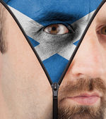 Unzipping face to flag of Scotland — Stock Photo