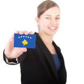 Business woman holding a card with the flag of Kosovo — Stock Photo