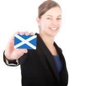 Business woman holding a card with the flag of Scotland — Stock Photo