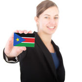 Business woman holding a card with the flag of South Sudan — Stock Photo