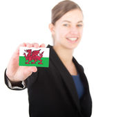 Business woman holding a card with the flag of Wales — Stock Photo