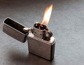 Silver metal lighter with flame. — Stock Photo