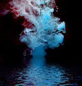 Blue ink reflected in water. — Stock Photo