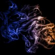 Stock Photo: Colorful smoke on black.