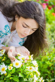 Young woman smelling flowers. — Stock Photo