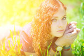 Redhead girl lay on grass. — Photo