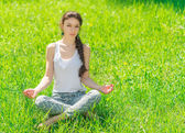 Young woman sitting in a lotus position. — Stock Photo