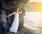 Woman in dress standing on beach and looking to the sea. — Stock Photo