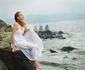 Vrouw zitten aan de kust op strand. — Stockfoto