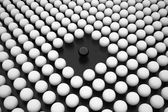 Black Sphere between Array of White Spheres — Stock Photo