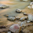 Stock Photo: Stream flows through small rocks