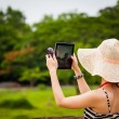 female tourist using an ipad to take photos in angkor wat temple — Stock Photo